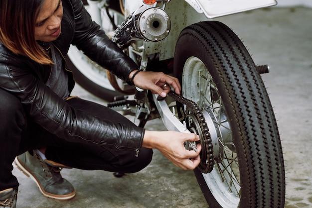 Motociclista asiática que fixa sua motocicleta antes de um passeio