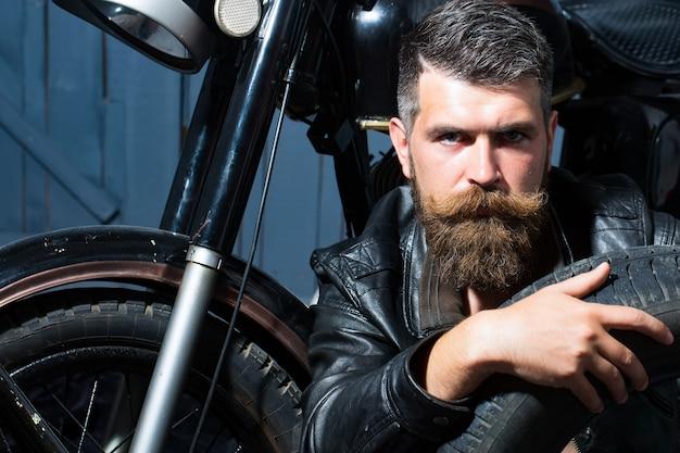 Motociclista barbudo bonito em uma jaqueta de couro sentado perto de uma motocicleta na garagem