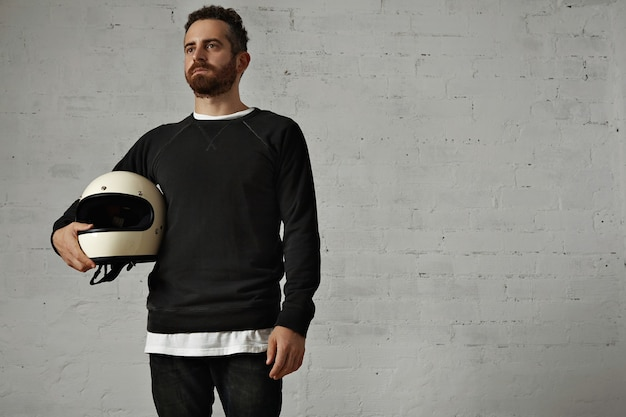 Motociclista barbudo em preto e branco segurando um capacete branco em branco sob o braço olhando para o futuro