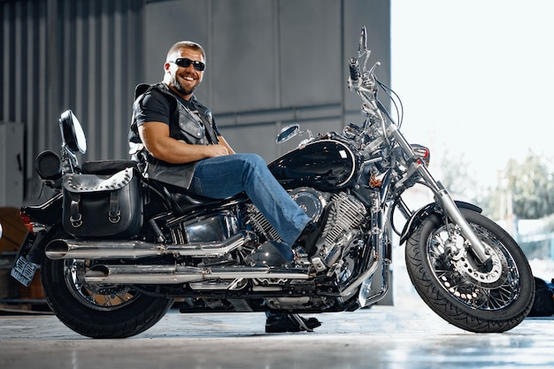Motociclista barbudo em roupas de couro preto com sua moto