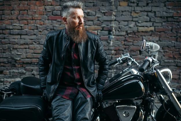 Motociclista barbudo posa em helicóptero clássico, transporte de duas rodas. piloto de moto vintage, estilo de vida de liberdade