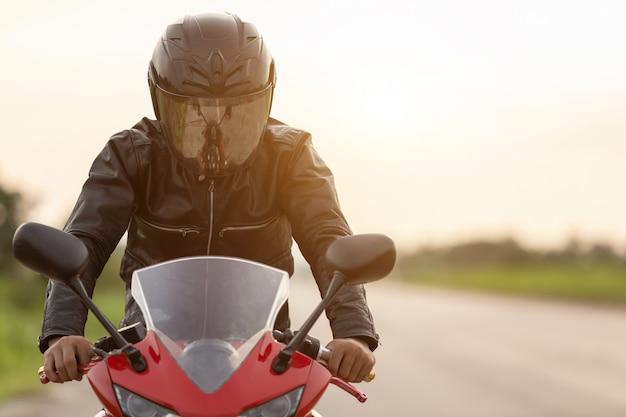 Motociclista bonito vestindo jaqueta de couro e segurando o capacete na estrada