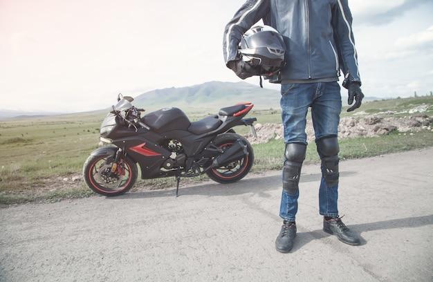 Motociclista caucasiano segurando capacete hobby sport