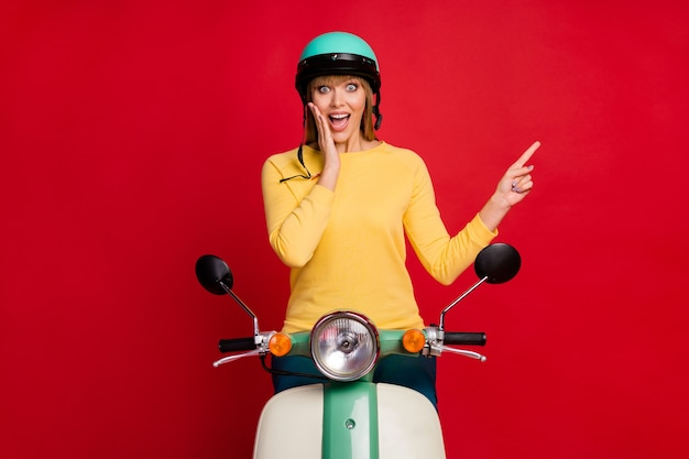 Motociclista chocada e enérgica louca em uma motocicleta indicando o espaço vazio do dedo