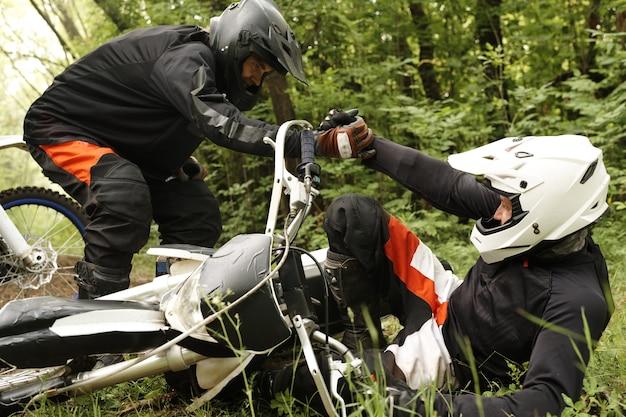 Motociclista com capacete ajudando amigo caído da motocicleta em um conceito de floresta, amizade e apoio