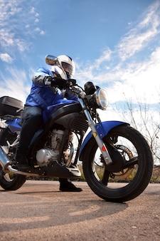 Motociclista com capacete azul passando por uma estrada