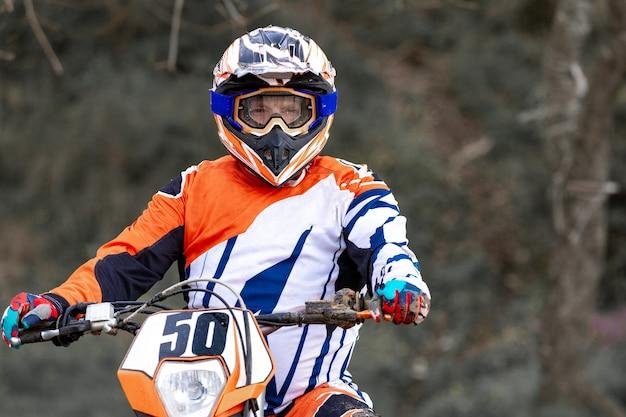 Motociclista com capacete e jaqueta de couro correndo na estrada