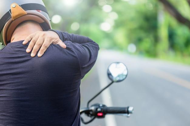 Motociclista com dor ou conceito cansado: piloto homem tocando em seu pescoço ou ombro e se sentindo cansado após um longo passeio de moto filmagem ao ar livre na estrada com espaço de cópia