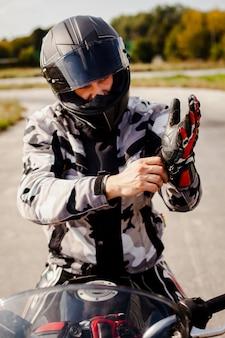 Motociclista cuidadosa, colocando o equipamento