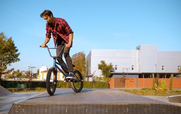 Motociclista de bmx fazendo truque, adolescente em treinamento no skatepark. esporte radical de bicicleta, exercícios de ciclismo perigosos, passeios de rua de risco, ciclismo no parque de verão