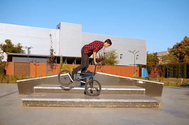Motociclista de bmx fazendo truque nas escadas, adolescente em treinamento no skatepark. esporte radical de bicicleta, exercícios de ciclismo perigosos, passeios de rua de risco, ciclismo no parque de verão