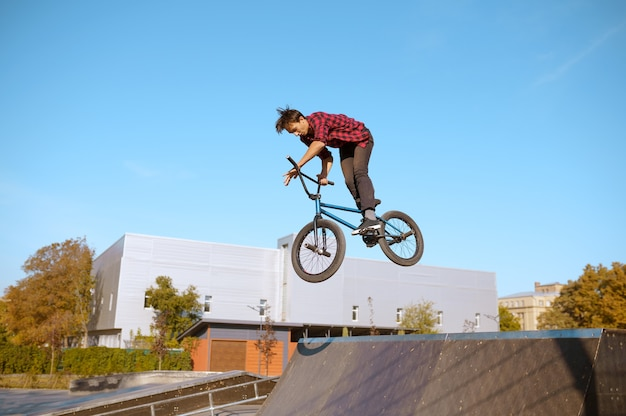 Motociclista de bmx masculino salta na rampa, adolescente em treinamento no skatepark. esporte radical de bicicleta, exercícios de ciclismo perigosos, passeios de rua de risco, ciclismo no parque de verão