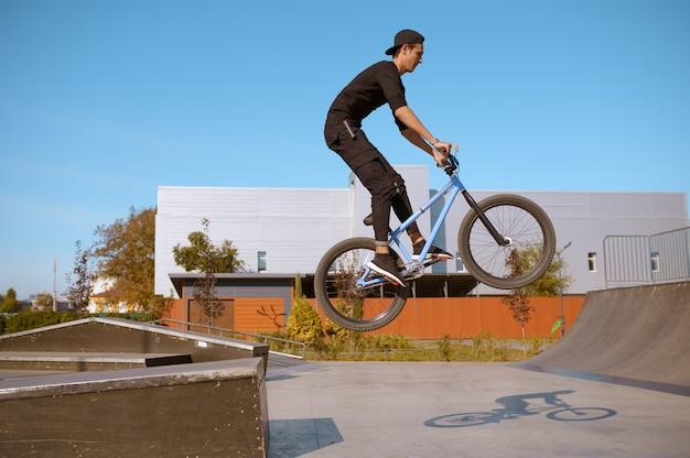 Motociclista de bmx masculino, salto em ação, adolescente em treinamento no skatepark. esporte radical de bicicleta, exercícios de ciclismo perigosos, passeios de rua de risco, ciclismo no parque de verão