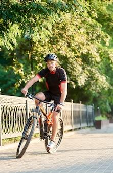 Motociclista de cara andando de bicicleta perto do parque verde