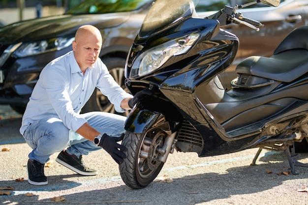 Motociclista de homem reparando motocicleta scooter na rua.