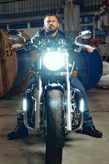 Motociclista de homem sentado em sua moto no estacionamento subterrâneo