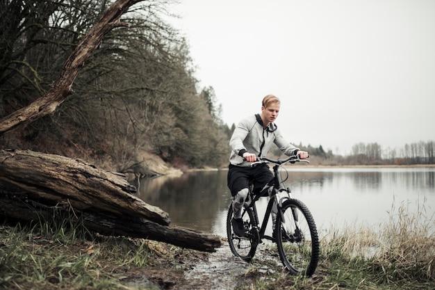 Motociclista de montanha, andar de bicicleta perto do lago