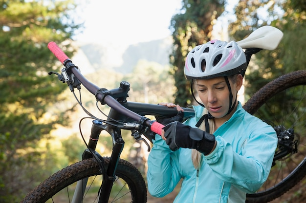 Motociclista de montanha feminino carregando sua bicicleta na floresta