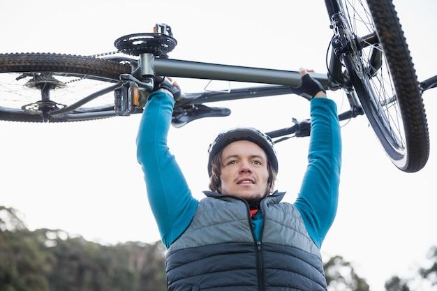 Motociclista de montanha masculino carregando bicicleta na floresta