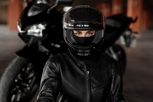 Motociclista de mulher dirigindo sua moto ou helicóptero de enduro, vestida com roupas de couro elegantes e equipamentos de proteção