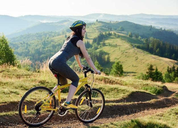 Motociclista de sorriso atraente da mulher que monta na bicicleta amarela na trilha rural nas montanhas, capacete vestindo, no dia de verão.