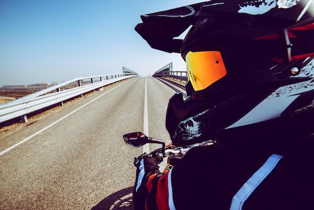 Motociclista em ação olhando para trás na estrada