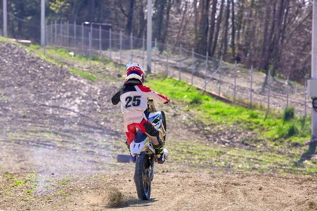 Motociclista em acrobacias de moto enquanto dirige na vista traseira da roda traseira