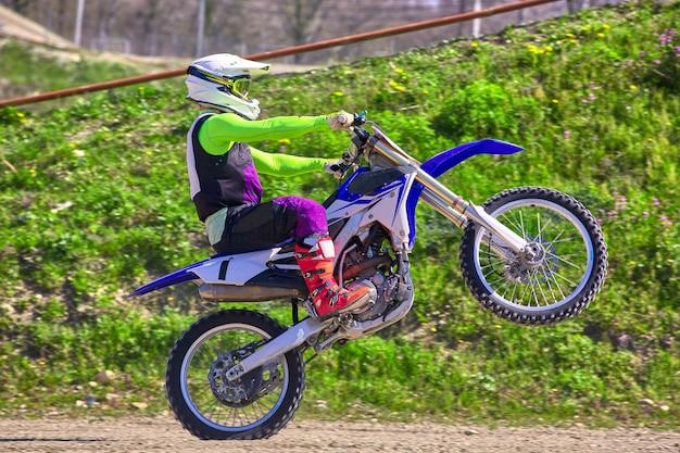 Motociclista em acrobacias de motocicleta enquanto dirigia na vista lateral da roda traseira