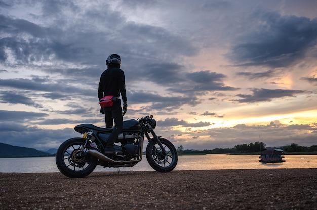 Motociclista em pé na bicicleta grande vintage com céu no reservatório