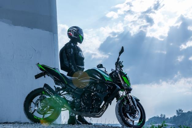 Motociclista em um capacete e em um traje de proteção fica debaixo da ponte