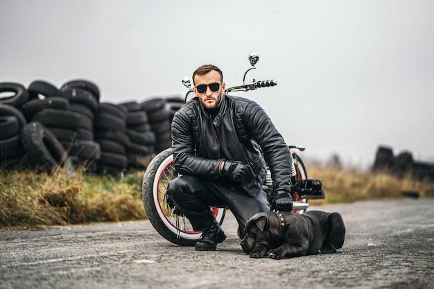 Motociclista em um terno de couro agachado perto de seu cachorro e moto vermelha na estrada. muitos pneus no fundo