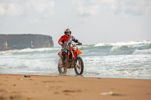 Motociclista em um traje de proteção anda de moto no mar, salpicos voam debaixo das rodas.