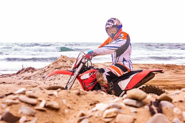 Motociclista em um traje de proteção sentado na moto em frente ao mar