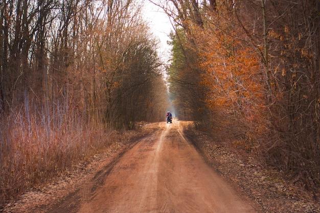 Motociclista em uma deslumbrante floresta de outono caminhando em um caminho natural