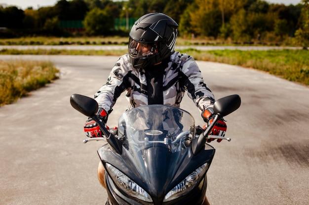 Motociclista esperando para atravessar a rua