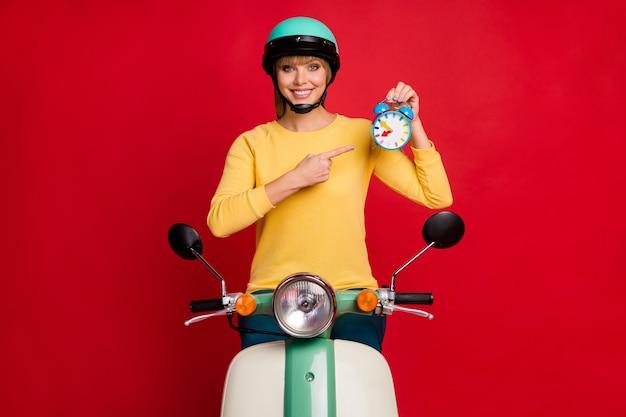 Motociclista esportiva positiva em uma motocicleta que aponta o relógio do dedo indicador