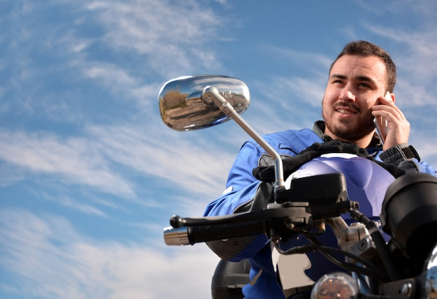 Motociclista, falando por telefone com seu telefone inteligente