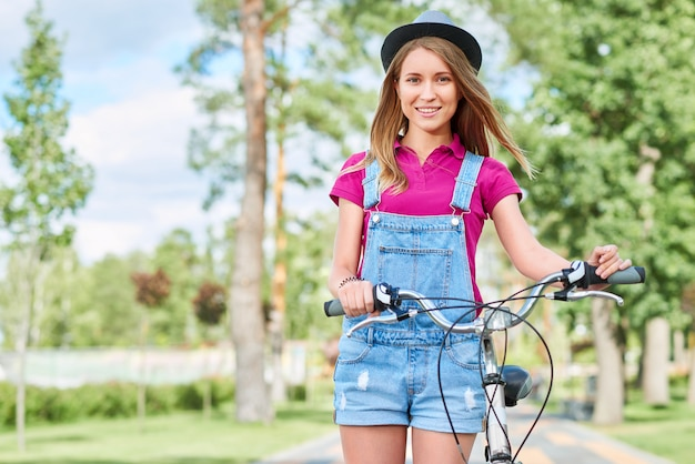 Motociclista fêmea alegre novo atrativo que sorri estando ao lado de sua bicicleta no parque em um conceito de viagem da atividade da recreação da fuga do turismo das férias mornas do copyspace do dia de verão.