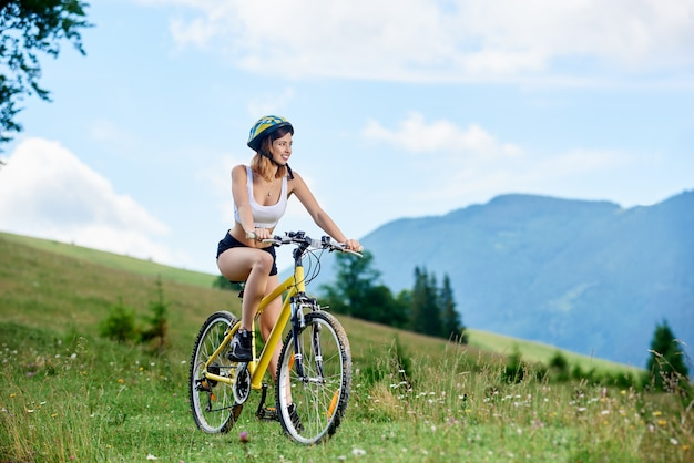 Motociclista feminina atleta feliz andando de bicicleta amarela nas montanhas