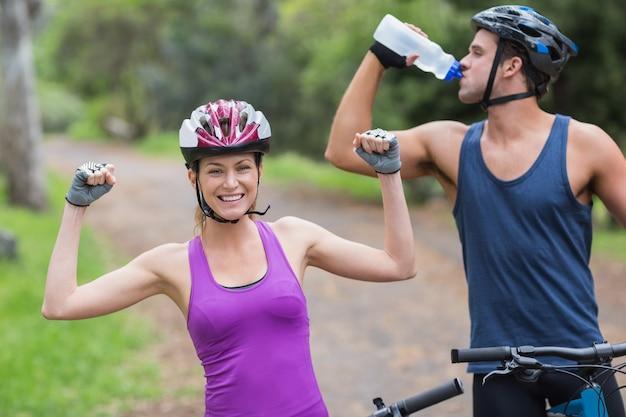 Motociclista feminina com água potável de homem na floresta