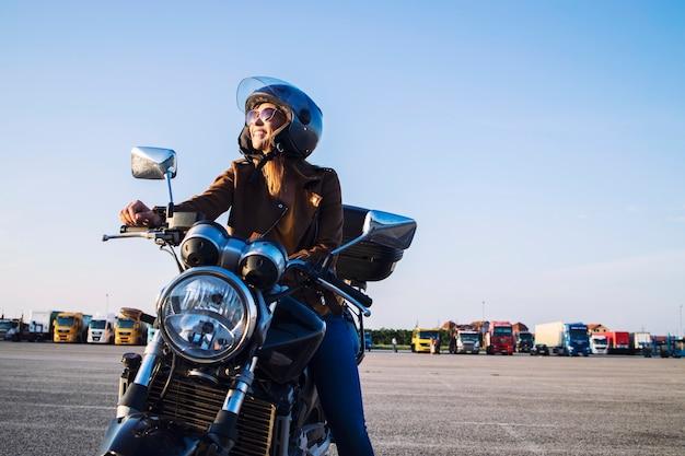 Motociclista feminina com jaqueta de couro e capacete sentada em uma motocicleta retrô e sorrindo