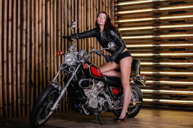 Motociclista feminina e menina bonita com cabelos escuros, cabelos compridos erótico desabotoando sua jaqueta de couro e shorts pretos e sapatos de salto alto encostado em uma motocicleta no fundo de uma parede de madeira