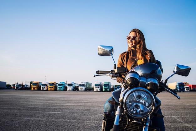 Motociclista feminina em uma jaqueta de couro, sentada em uma moto retrô e sorrindo