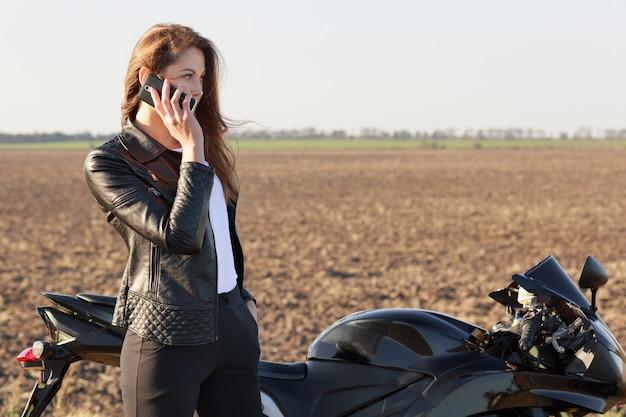 Motociclista feminina tem conversa ao telefone, para na estrada, posa perto de moto, discute as últimas notícias com o amigo, vestida de jaqueta de couro e calça preta. conceito de tecnologia e transporte