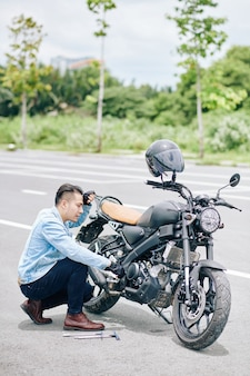 Motociclista frustrado consertando sua bicicleta quebrada na estrada