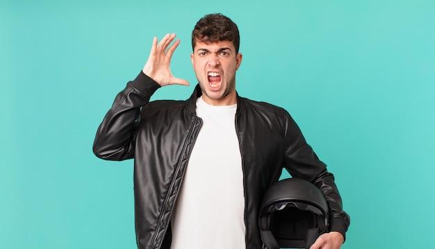 Motociclista gritando com as mãos para o alto, sentindo-se furioso, frustrado, estressado e chateado