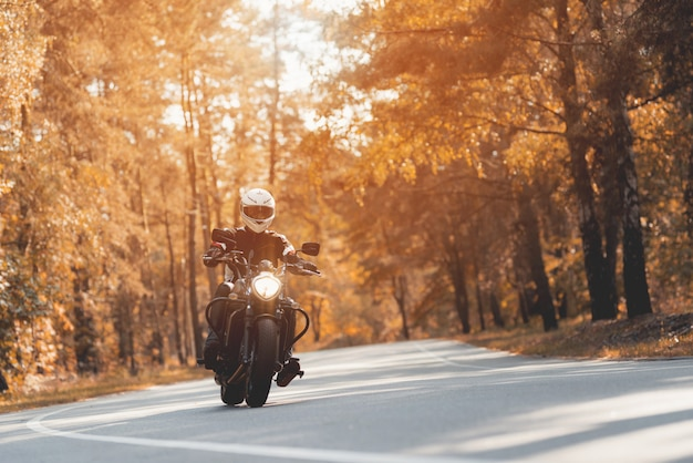 Motociclista masculina que monta a motocicleta preta brilhante