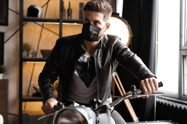 Motociclista masculino bonito e brutal com máscara preta e jaqueta de couro sentado em uma motocicleta olhando para frente