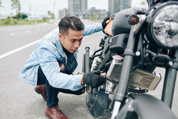 Motociclista muito preocupado, verificando o motor da motocicleta e procurando por defeitos