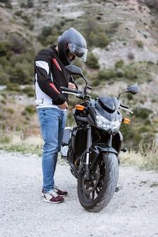 Motociclista novo que põe sobre seu revestimento antes de conduzir sua motocicleta.